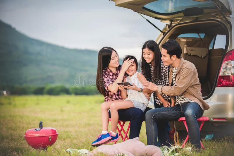 Happy little girl with asian family sitting in the car for enjo. Ying road trip and summer vacation in camper van stock image