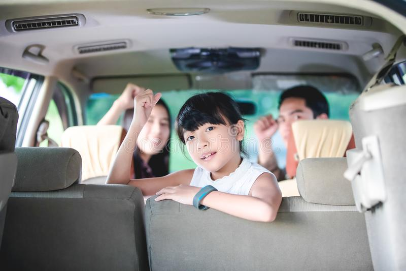 Happy little girl with asian family sitting in the car for enjo. Ying road trip and summer vacation in camper van royalty free stock images