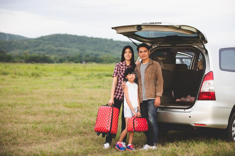 Happy little girl with asian family sitting in the car for enjoying road trip and summer vacation in camper van.  royalty free stock images