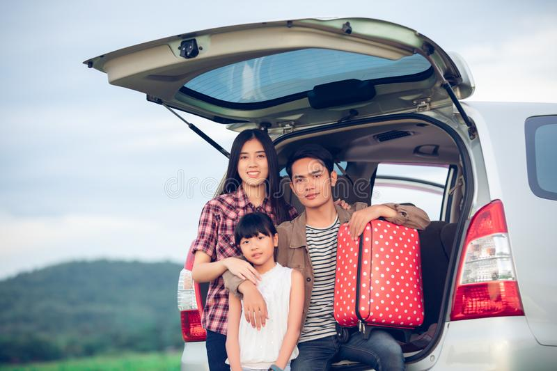 Happy little girl  with asian family sitting in the car for enjoying road trip and summer vacation in camper van stock photos
