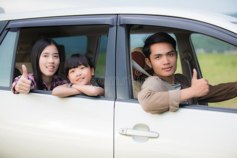 Happy little girl with asian family sitting in the car for enjo. Ying road trip and summer vacation in camper van royalty free stock photography