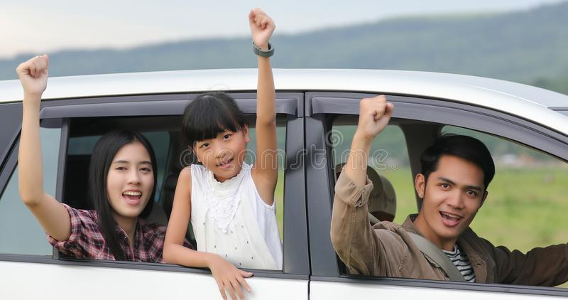 Happy little girl with asian family sitting in the car for enjo. Ying road trip and summer vacation in camper van royalty free stock image