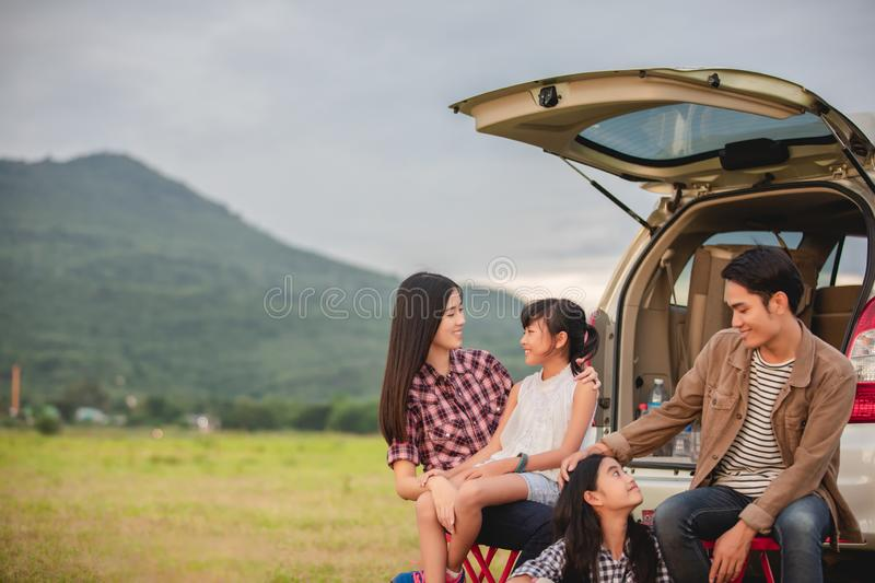 Happy little girl  with asian family sitting in the car for enjoying road trip and summer vacation in camper van royalty free stock images