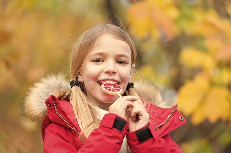 Happy little girl in autumn forest. Feeling protected at this autumn day. Small child with autumn leaves. Little girl. Eat lollipop. Autumn fashion. Happy stock image