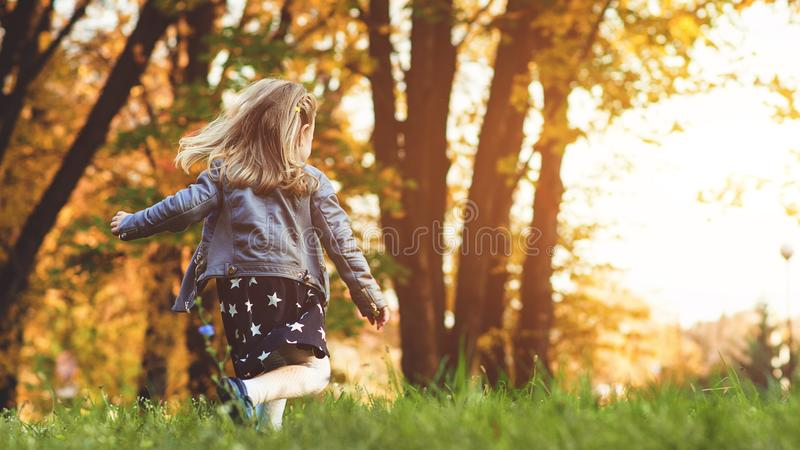 Happy little girl in autumn. Funny child playing outdoors. Autumn fashion. Autumn holidays. Happy childhoood royalty free stock photography