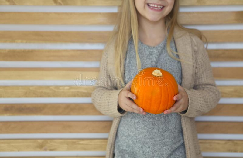 Happy little girl with autumn pumpkin by the wooden wall background royalty free stock photo