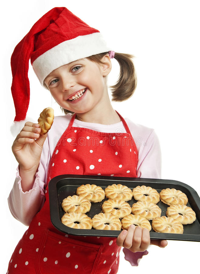 Happy little girl baking Christmas cookies. White background royalty free stock photography