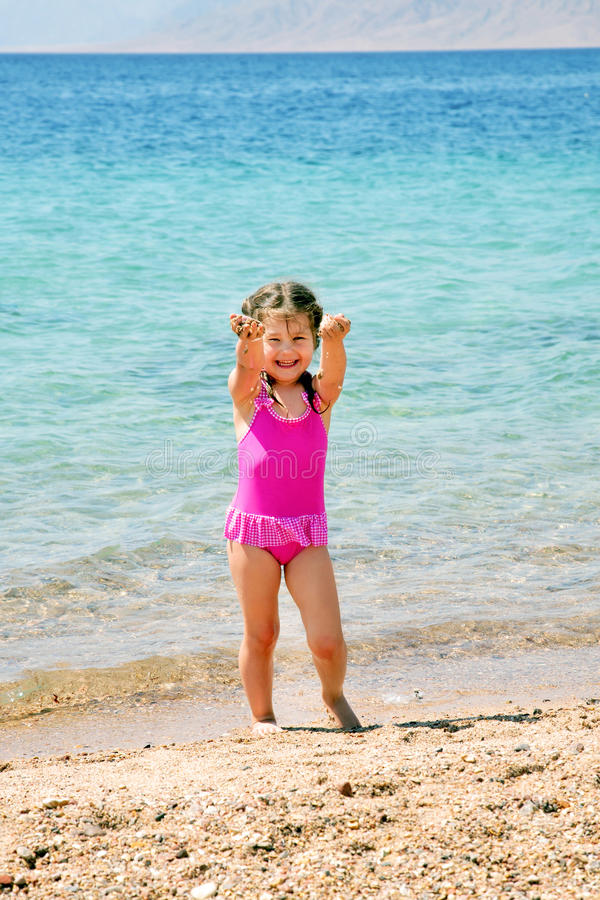 Happy little girl on the beach playing royalty free stock photography