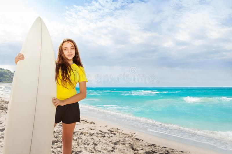 Girl with surfing board on the sea. Happy little girl on the beach standing with surfing board near the ocean royalty free stock photo