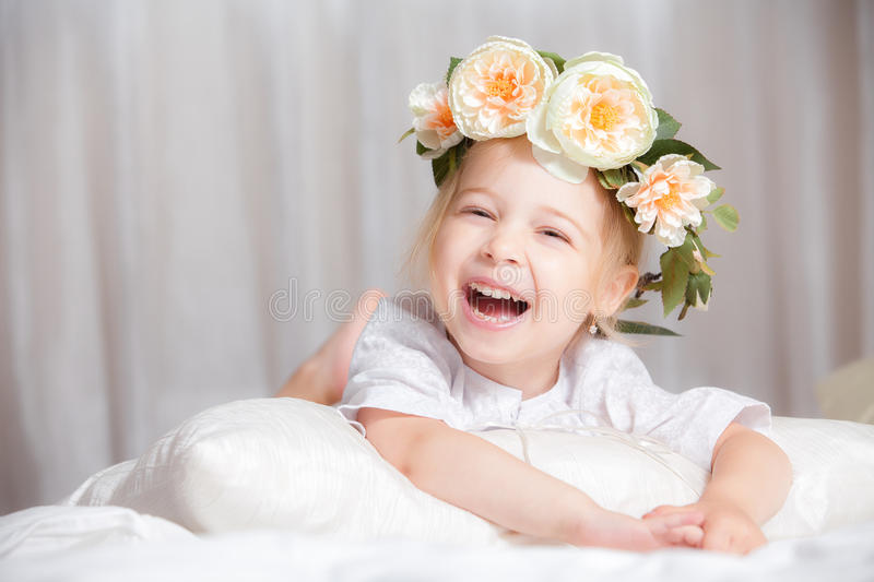 Happy little girl on a bed royalty free stock photography