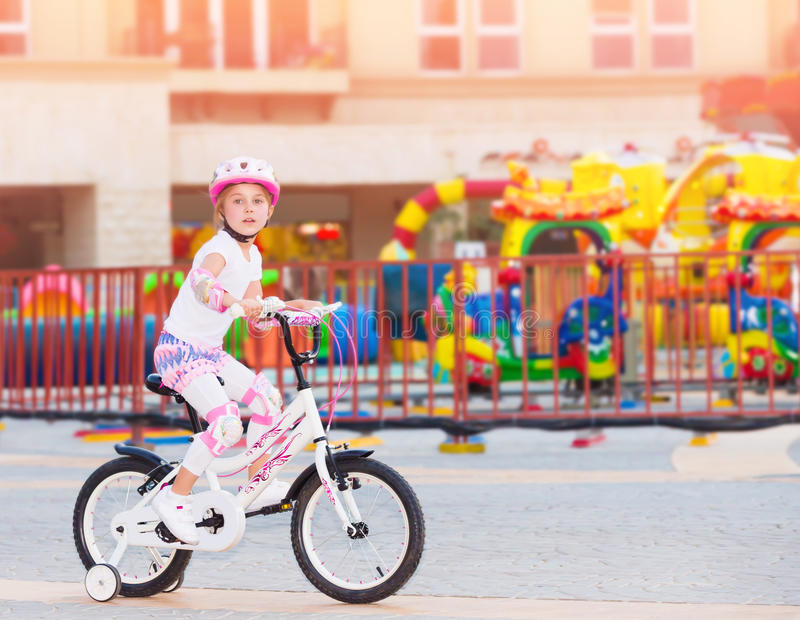 Happy little girl on the bicycle stock photos