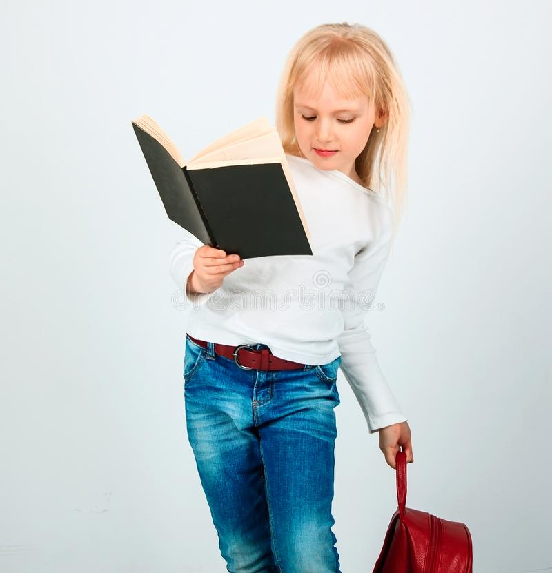 Happy little girl with a big book and a red backpack is jumping royalty free stock photo