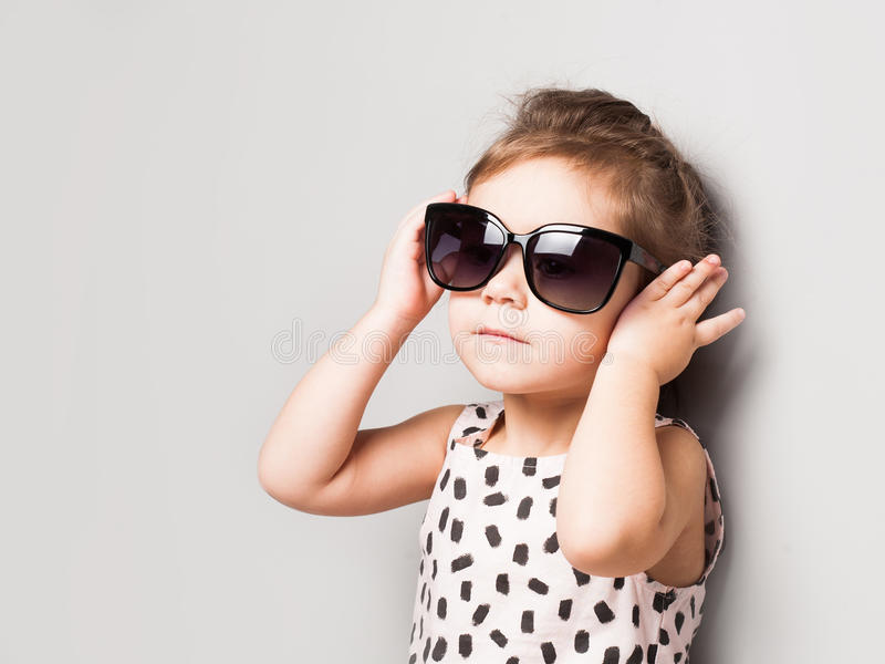 Happy little girl with big sunglasses. Fashionable baby stock photo
