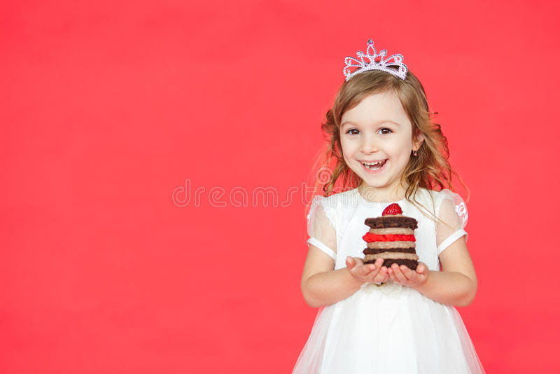 Happy little girl with birthday cake isolated on red background. With copy space. Kid celebrating her birthday with a mini cake royalty free stock photos