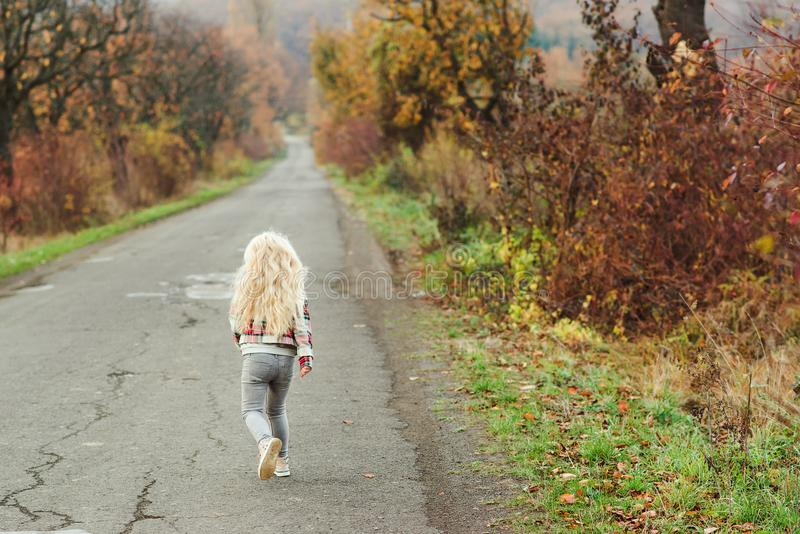 Happy little girl with blonde long hair running away on the road, back view. Walk in autumn time. Stylish fashion child outdoors. stock image