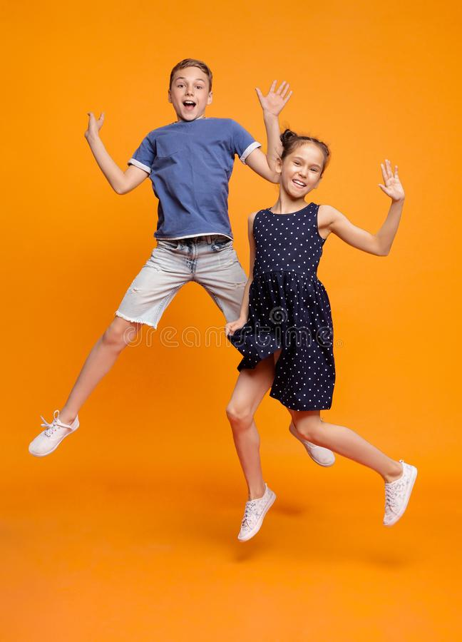 Happy little girl and boy jumping for joy together royalty free stock images