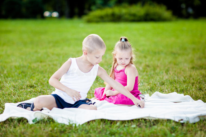 Happy little girl and boy in a park royalty free stock image