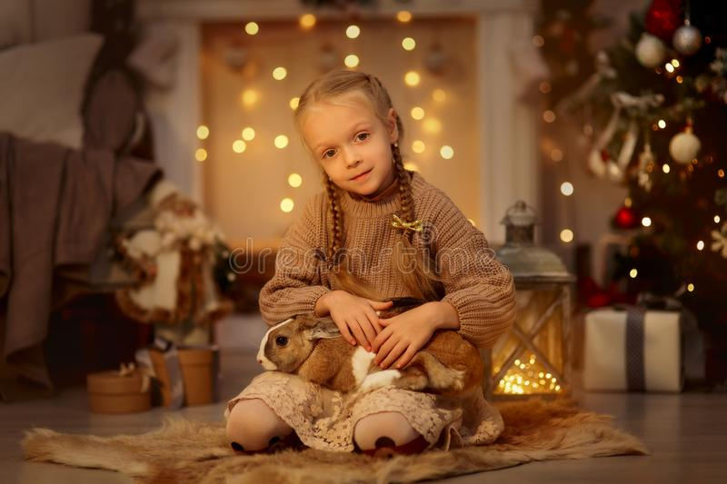 Happy little girl with brown rabbit at Christmas eve stock photo