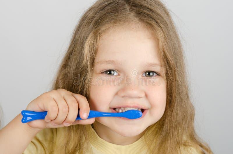 Happy little girl brushing her teeth stock images