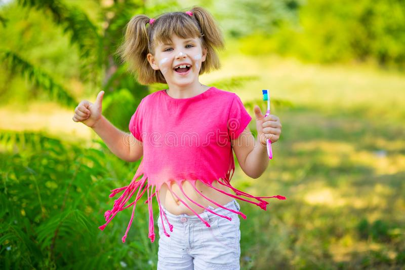 Happy little girl brushing her teeth with thumbs up. Dental hygiene. stock photo