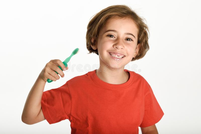 Happy little girl brushing her teeth with a toothbrush. Isolated on white background. Studio shot stock photo