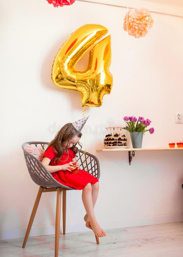 Happy little girl celebrating the fourth birthday at home royalty free stock photo
