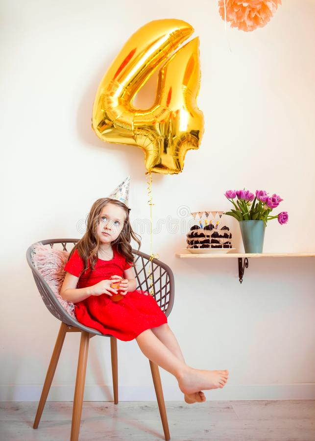 Happy little girl celebrating the fourth birthday at home.  royalty free stock image
