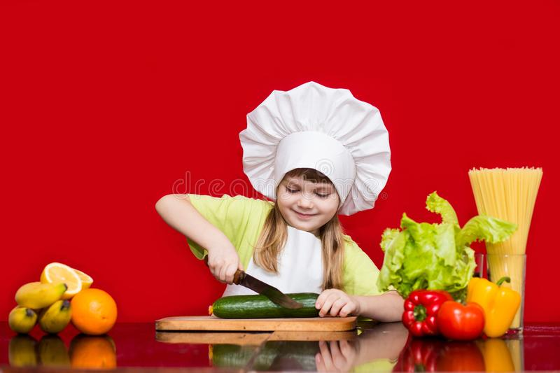 Happy little girl in chef uniform cuts vegetables in kitchen stock photos