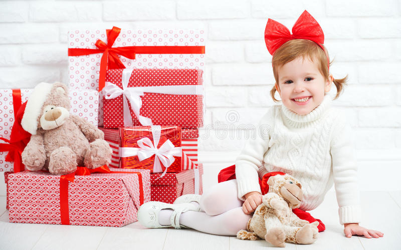 Happy little girl child with Christmas gifts at wall. Happy little girl child with Christmas gifts at a blank brick wall royalty free stock image