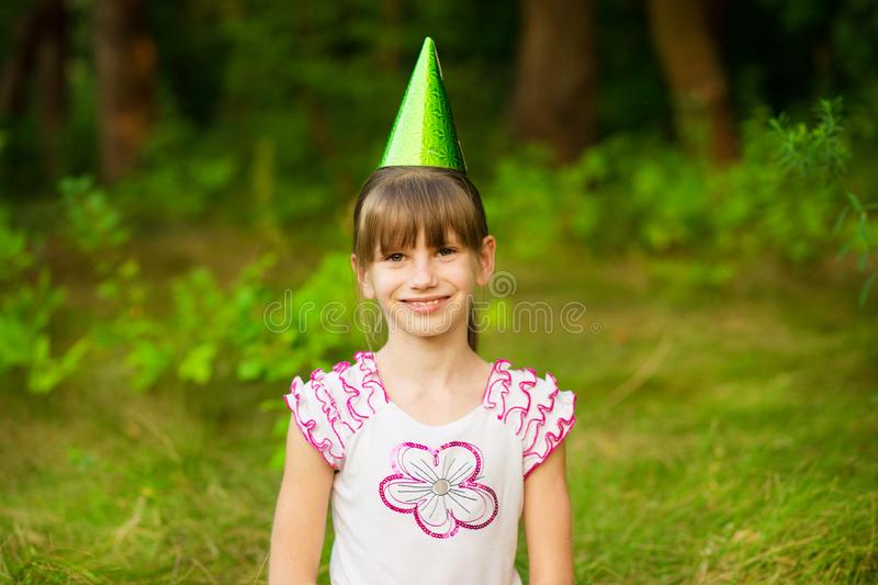 Happy little girl child cute and beautiful in festive cone caps, sit on grass, have fun stock image