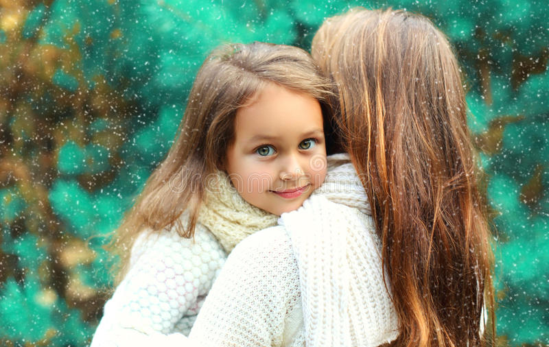 Happy little girl child hugging her mother in winter over tree stock image