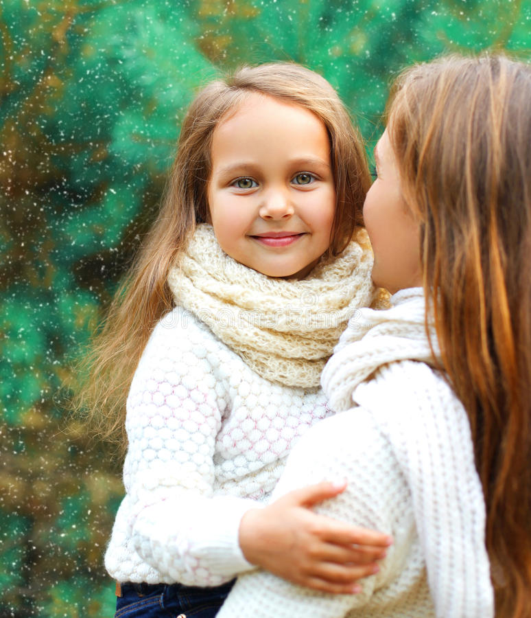 Happy little girl child hugging mother in winter day royalty free stock images
