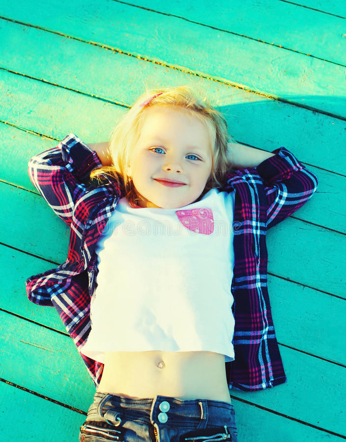 Happy little girl child resting on a wooden floor stock photos