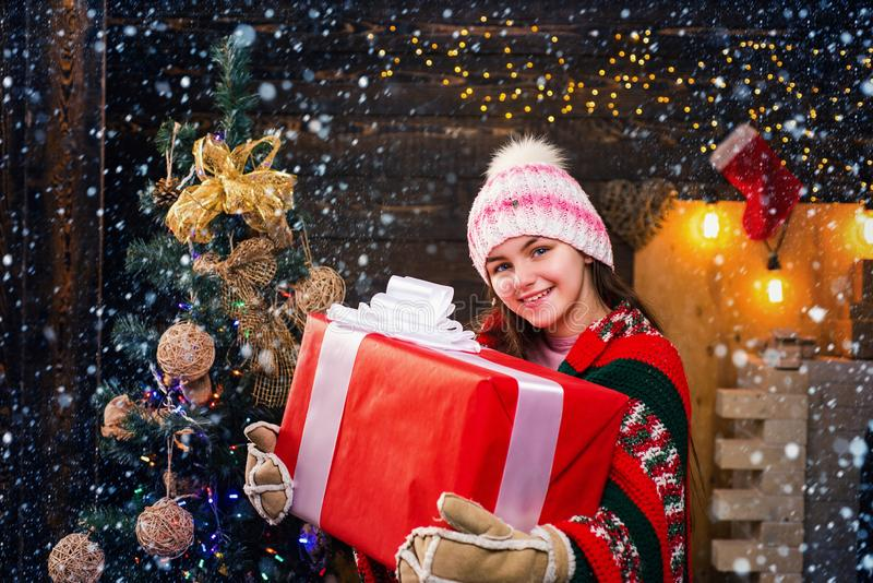 Happy Little girl with a Christmas present on wooden background. Child happiness celebrate New Year. Daughter hold. Parent from Parent. Christmas story concept royalty free stock photos