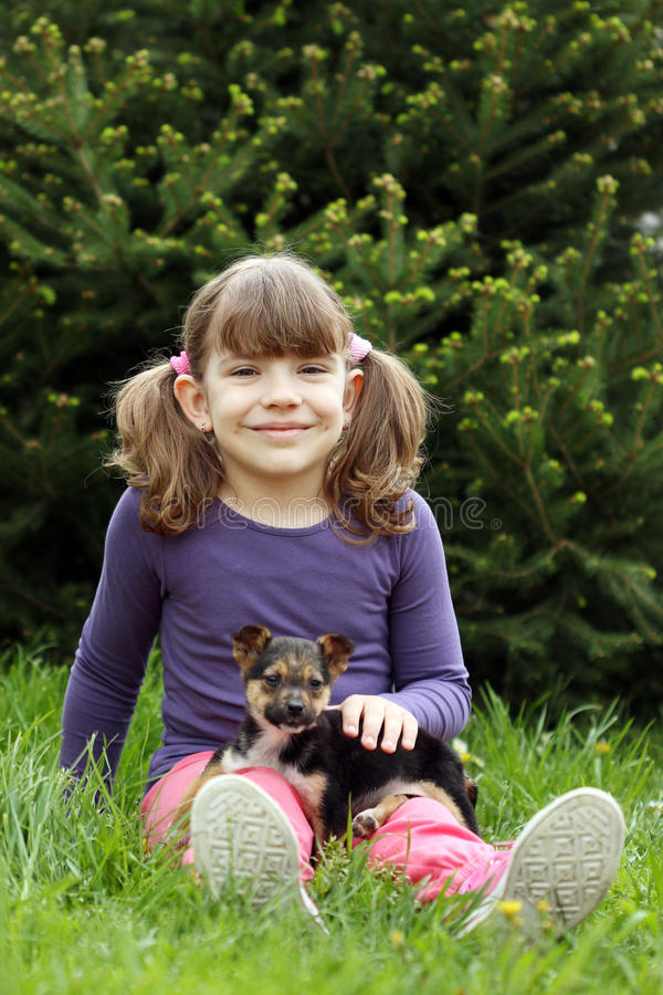 Happy little girl with cute puppy stock image