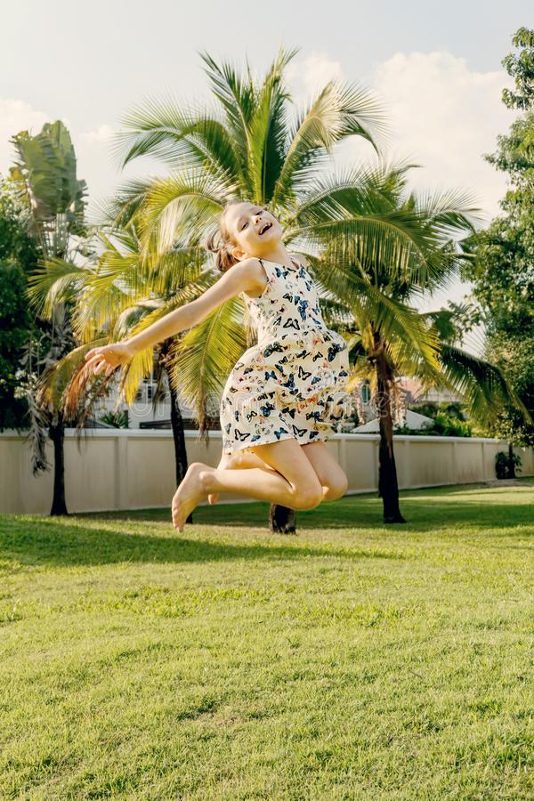 Happy little girl in dress jumping in front of palm trees. Joy, fun, travel concept. Warm summer colors stock photos