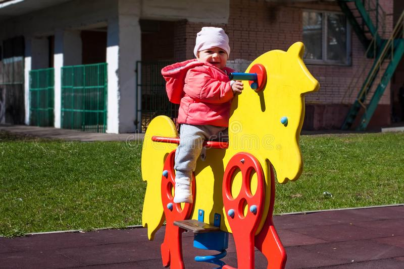 Happy little girl dressed in a pink jacket is sitting on a yellow toy horse. Baby plays on the playground, sits on the spring royalty free stock image