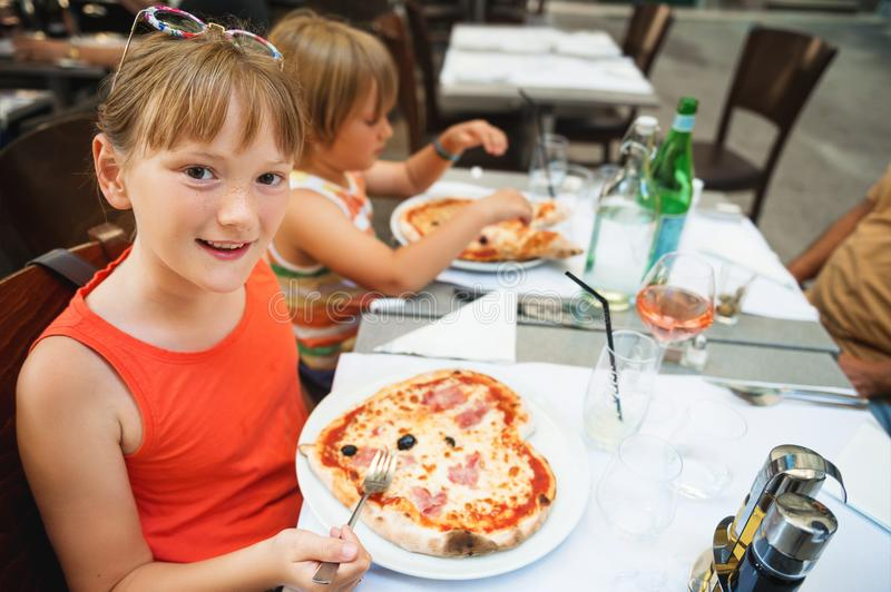 Happy little girl eating kid`s pizza in the restaurant stock photos