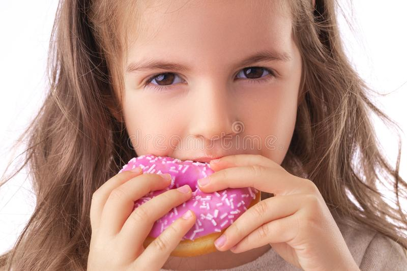 Happy little girl eating pink donut royalty free stock photo