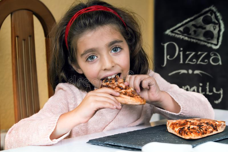 Happy little girl eating pizza in a restaurant stock image