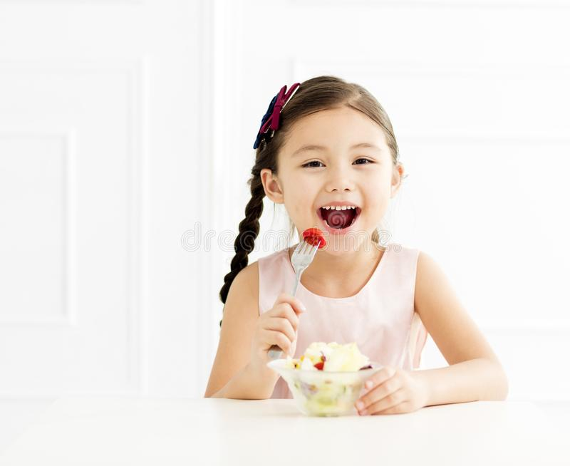 Little girl eating vegetable salad royalty free stock photo