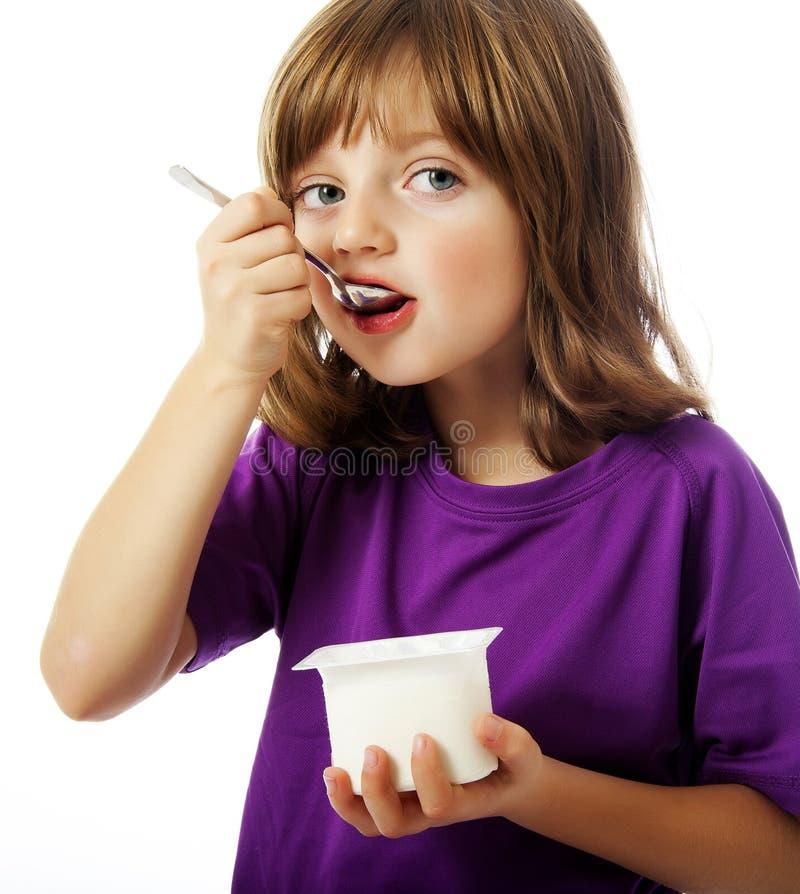 A Happy Little Girl Eating A Yogurt Stock Image