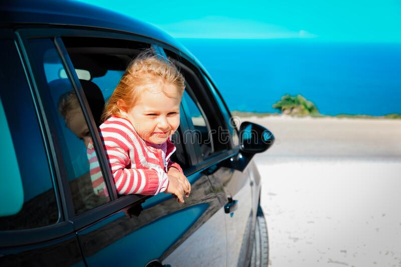 Happy little girl enjoy travel by car at sea royalty free stock photography