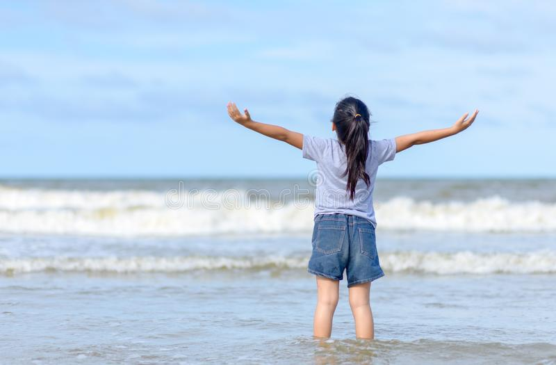 Happy little girl enjoying freedom with open hands on sea royalty free stock photography