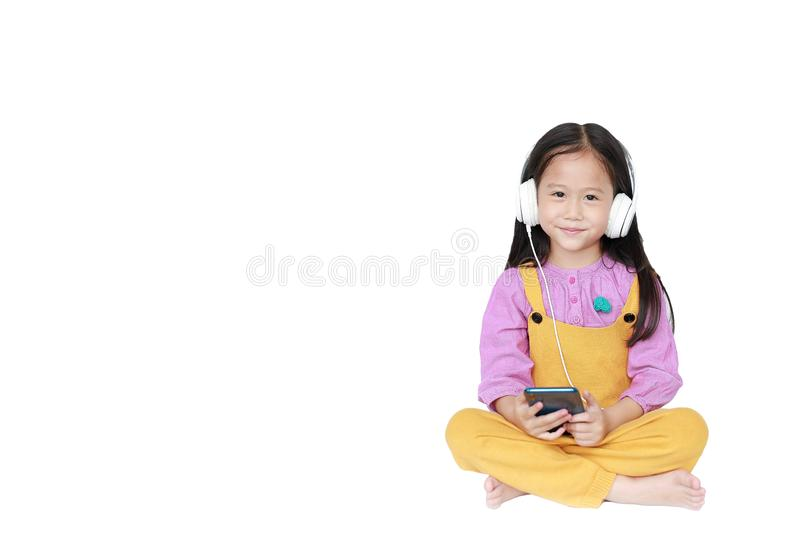 Happy little girl enjoys listening to music with headphones isolated on white background with copy space stock photography