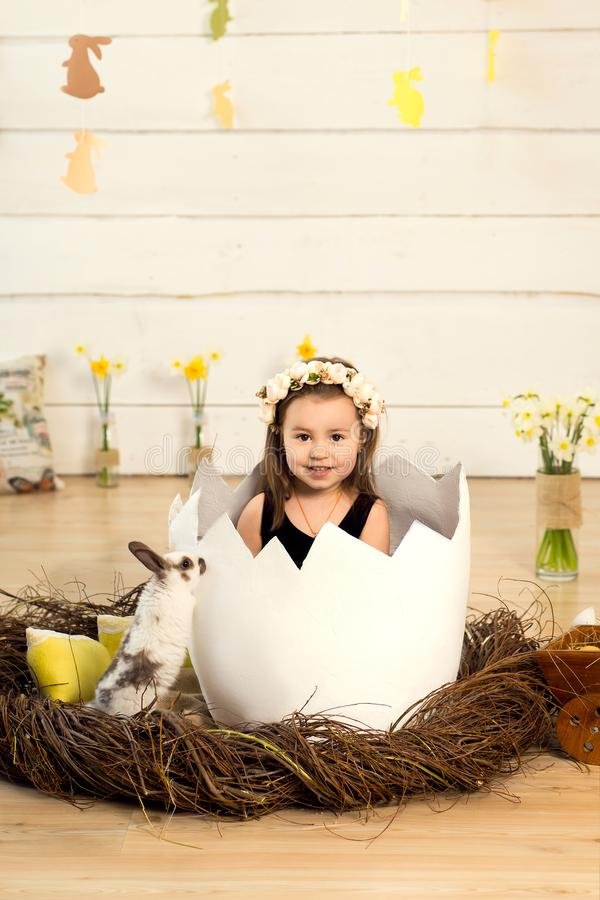 A happy little girl with flowers on her head is sitting in a decorative egg with cute fluffy Easter bunny. Easter egg in the stock photos