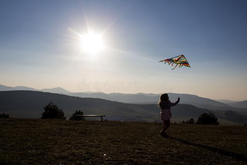 Happy little girl flying a kite on a hill of mountain Zlatibor, Serbia. royalty free stock photo