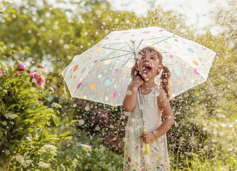 Happy little girl in garden under the summer rain with an umbrella royalty free stock image