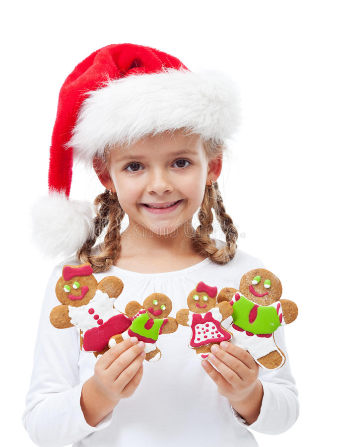 Happy little girl with gingerbread people family. Happy little girl with santa hat holding gingerbread people family royalty free stock image