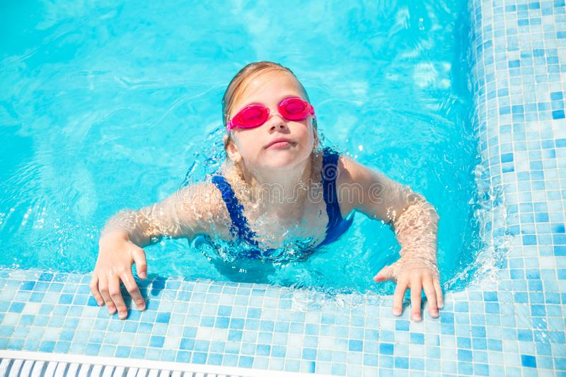Happy little girl in goggles playing in swimming pool Beach resort, summer vacation, travel and tourism concept stock photography